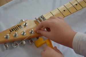 弦を抑えながらペグを回す